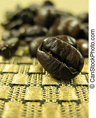 Bean close up - Detail of coffee beans on gold cloth Shallow...
