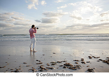 Photographing Beach - A photographer taking a photo on the...