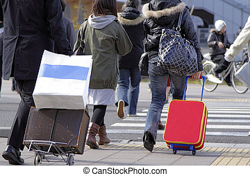 Travellers - People with suitcases crossing the street in a...