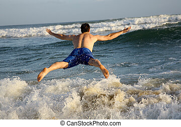 Action Man - A man jumping into the waves of the ocean