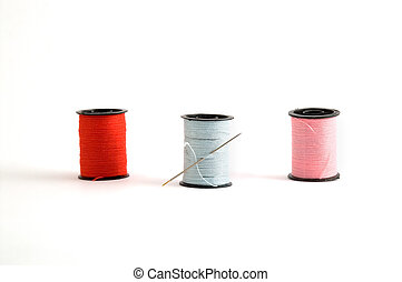 Sewing thread spools - 3 sewing thread spools and a needle.