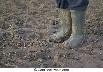 Muddy Wellies - Close crop image of some rubber boots on a...