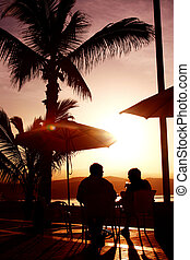 Sunset Drink - Couple at beachside cafe having a drink under...