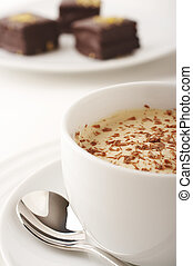 Coffee cup with cream and chocolate cakes