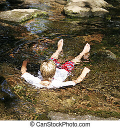 Boy Soaking In Spring - A blond boy taking a cold soak in...