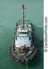 Tugboat waiting standby with rope to shore. Front, aerial...