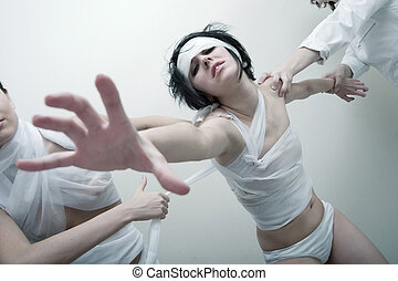 psycho girl - Young girl in bandage struggling out of hands...