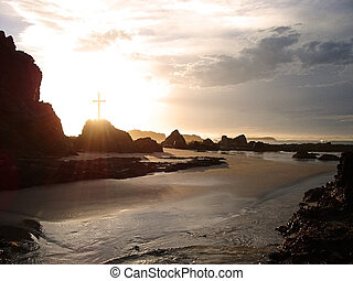 glowing cross by the sea - Rays of light pass through a...