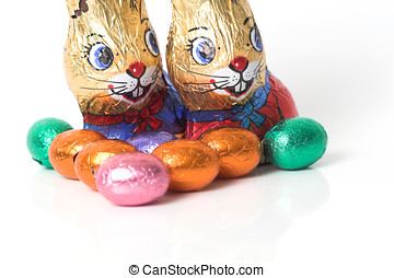 Chocolate bunnies overlooking the easter eggs on white...