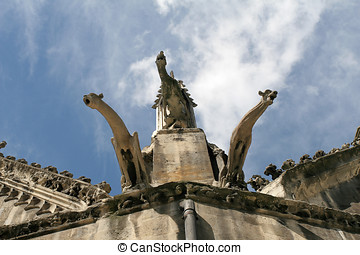 Three gargoyles on church roof against blue sky