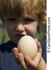 Egg Static - A young boy holds a newly laid egg up to the...