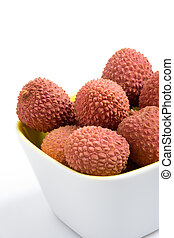 Fresh litchis in a cup on a white background