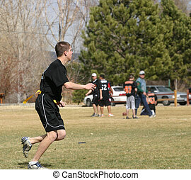 Flag Football Player - Young man playing flag football in a...