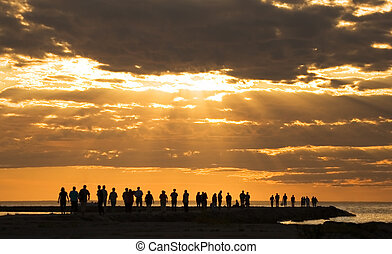 under the sun - group of people enjoying the sunset at...