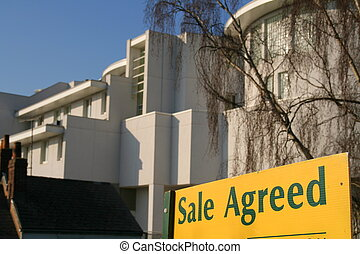 Sale Agreed - Real Estate Agents board in front of a modern...