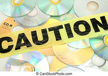 computer crime pirate - plastic caution tape and CD,...
