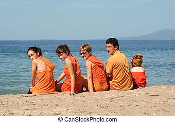 People on the beach - People in orange clothes on the beach