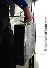 safe - businessman holding a briefcase with handcuffs tied...