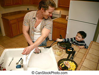 Doing Dishes - Toddler boy helping dad do the dishes. Focus...