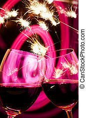 cocktail - two wineglasses with some wine in it in fireworks...