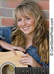 Young Musician - A pretty young woman resting on an acoustic...