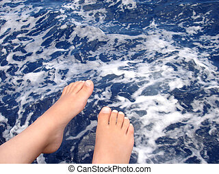 feet - boy sitting on a boat with his feet above the ocean
