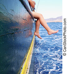 Relax - boy sitting on the ship�s rail with his legs above...