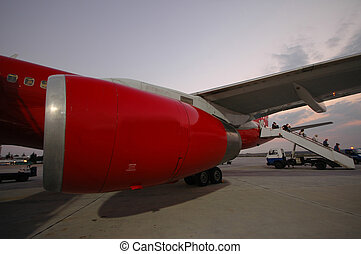 Red plane in an airport.