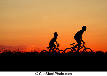 Summer Curfew - Silhouette of children on bikes at sunset