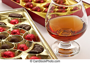 Glass with cognac and sweets with liquor isolated on a white...