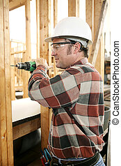 Carpenter Drilling Safely - A carpenter on a construction...