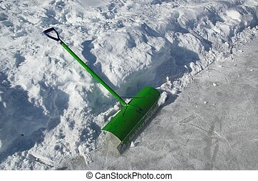 Snow shovel used for clearing ice on outdoor skating rink.