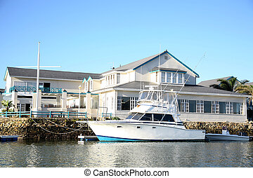 Boat House - A white beach house with a boat docked next to...