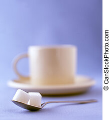 two sugar cubes with a cup of coffee on a saucer - Coffee...