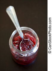 Cranberry Sauce - Cranberry sauce in a jar with a silver...