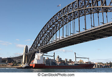 Sydney Harbour Bridge - Cargo ship passing under the Sydney...