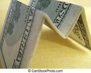 Perception - Hundred dollar bills folded in m shape on a...