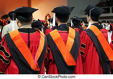 Three Asian university graduates in gowns