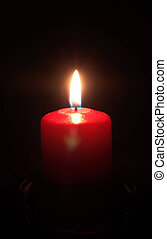 red candle light on black background in a glass holder