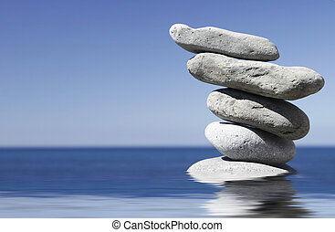 Pebble Stack - Stack of pebbles in shallow water with blue...