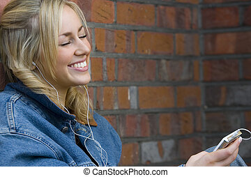Happy Listening - A beautiful young woman happily listening...