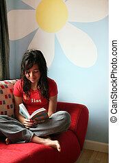 Girl reading at home - Teenage girl reading a book on a sofa...
