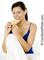 Eating Cracker - A pretty young woman sitting and eating a...