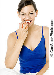 Healthy Eating - A young woman in blue eating a red apple on...