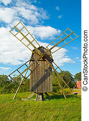 windmill on green gras and blue sky with white clouds