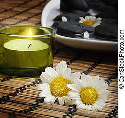 daisies and candle before pebbles - candle and two daisies...