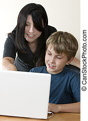 Adult woman and child at computer - Adult woman helps a...