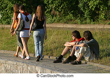 Teenagers - Three girls walk and of them observe two young...