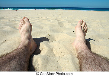 relaxing - man hairy legs on beach, water and people in...