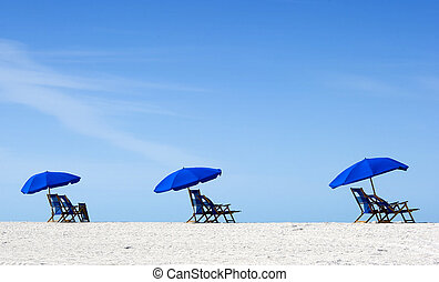 Empty Beach - Three beach umbrellas and empty chairs on...